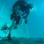 NEEMO engineering crew diver simulates anchoring to an asteroid surface.